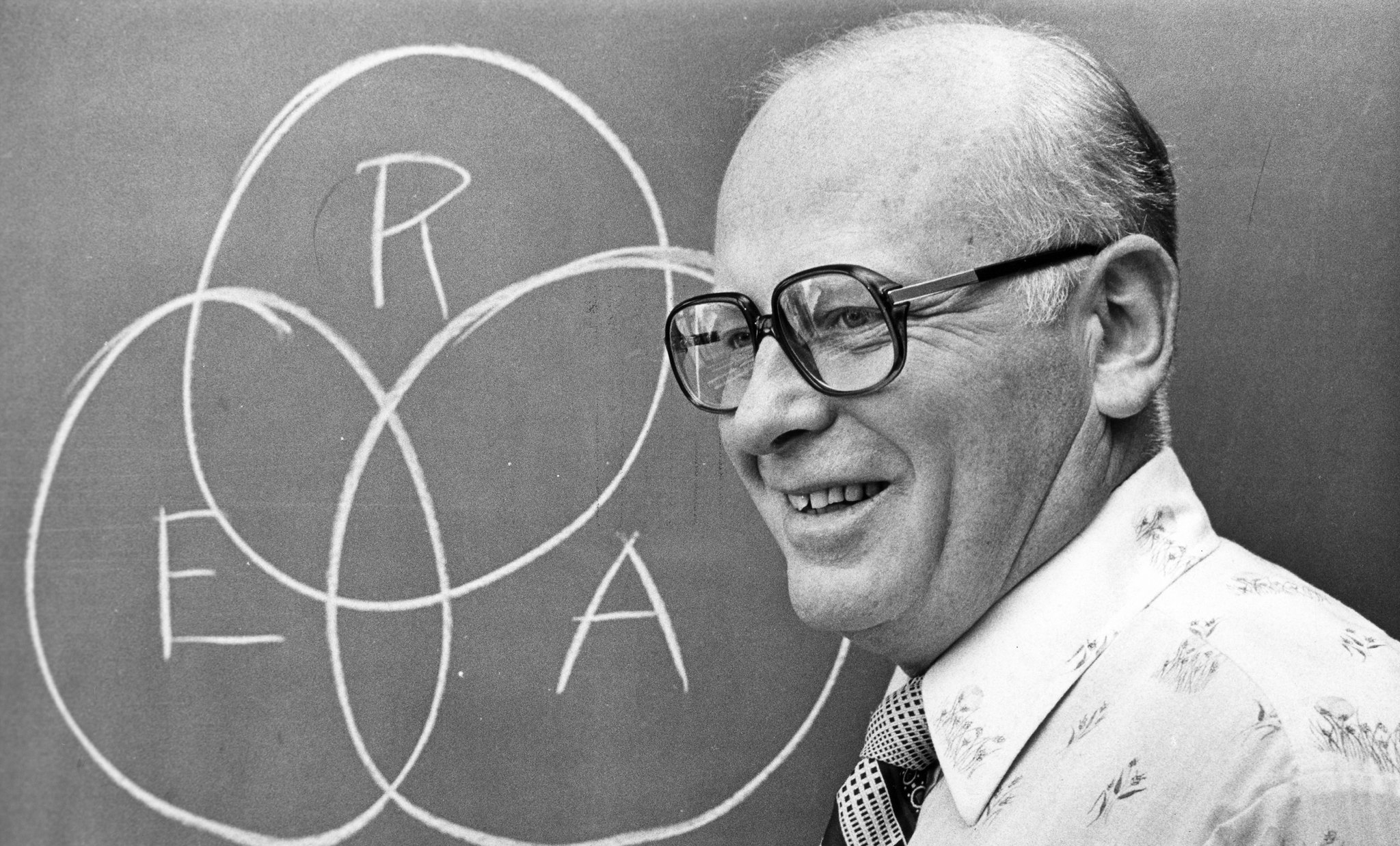 Historic photo of Bill Wick standing in front of a black board wtih the large letters R, E and A written on it.