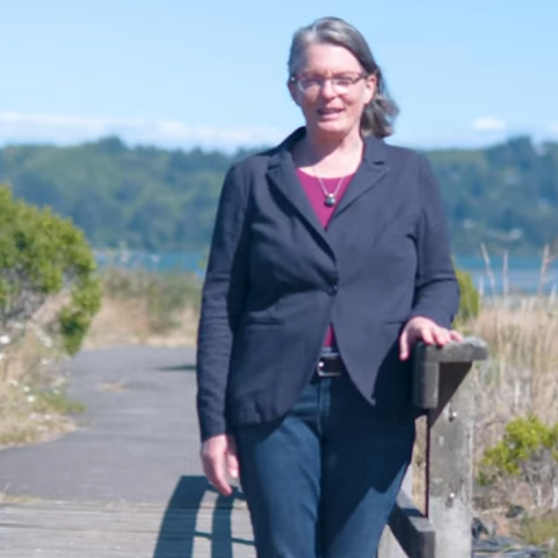 Caren Braby stand by a walking path near the Yaquina Bay in Newport, Oregon on a sunny and breezy day.