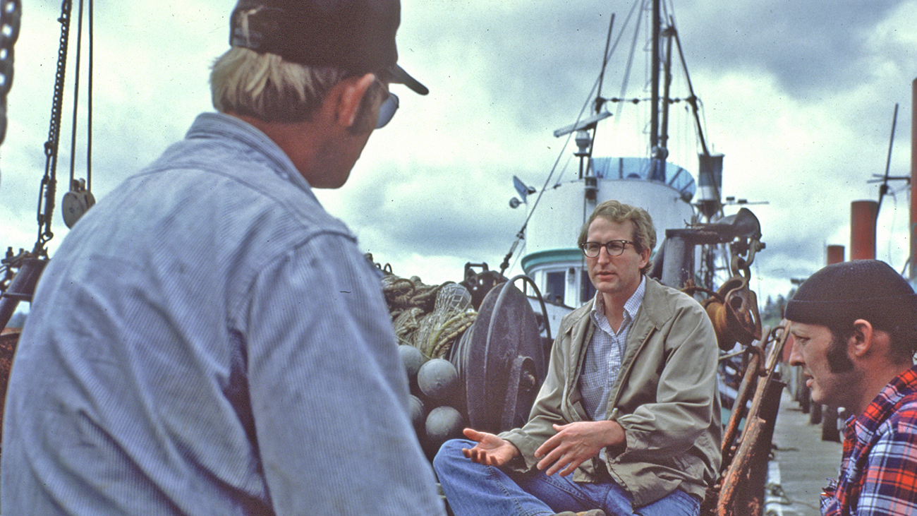 A photo from the 1970s shows three men talk on a commercial fishing dock. A large fishing boat is in the background.