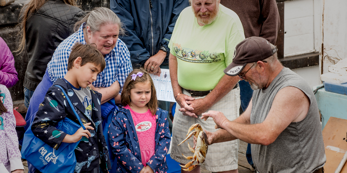 fisherman with crab show it to visitors on the dock