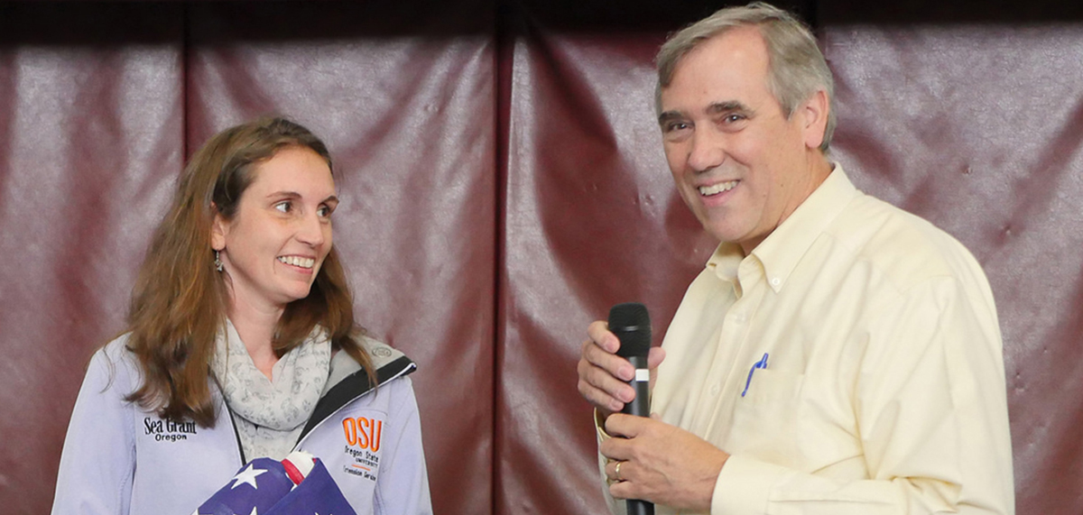 U.S. Sen. Merkley presents a flag to Oregon Sea Grant Extension marine fisheries specialist Kaety Jacobson at a Newport town hall. (Photo by Tiffany Woods)