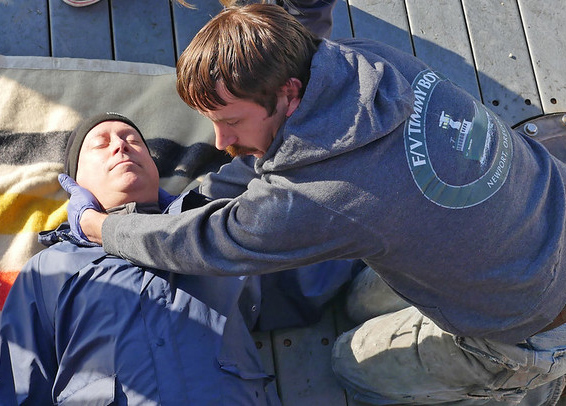 Jason Jones (right) assesses the condition of participant during a simulation aboard a boat in Newport.