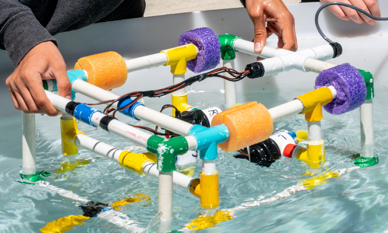 Hands immerse a remotely operated underwater device into a tank of water to test it during a day camp.