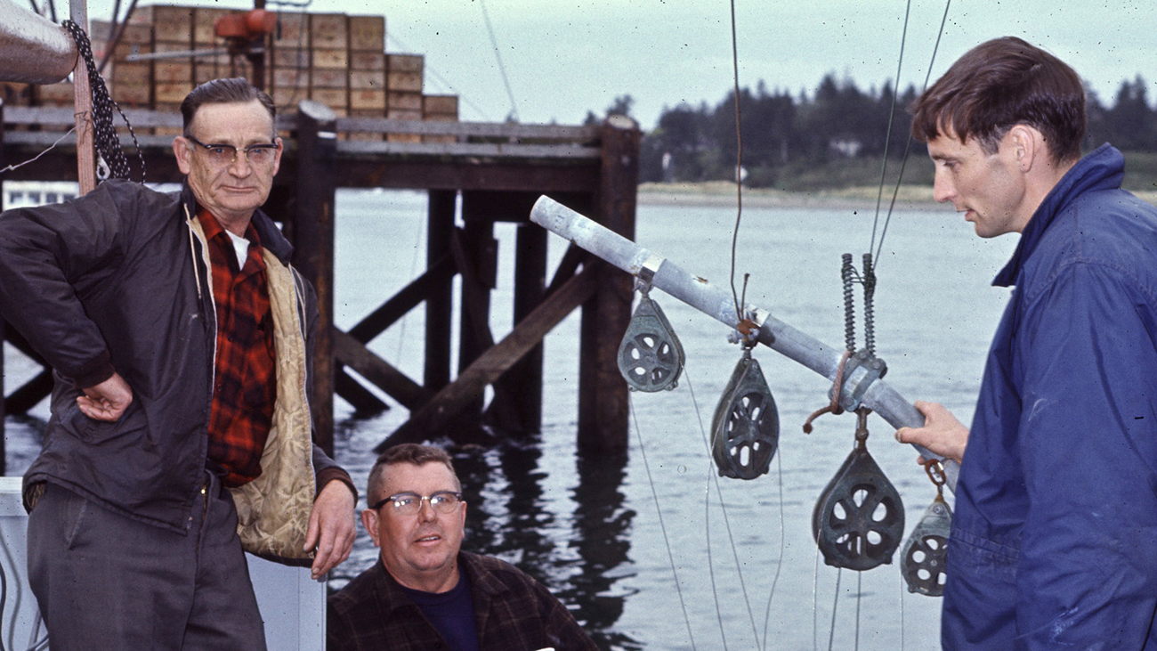Three men on a commercial fishing dock in the 1970s. A pier with stacked wooden crates is in the background.