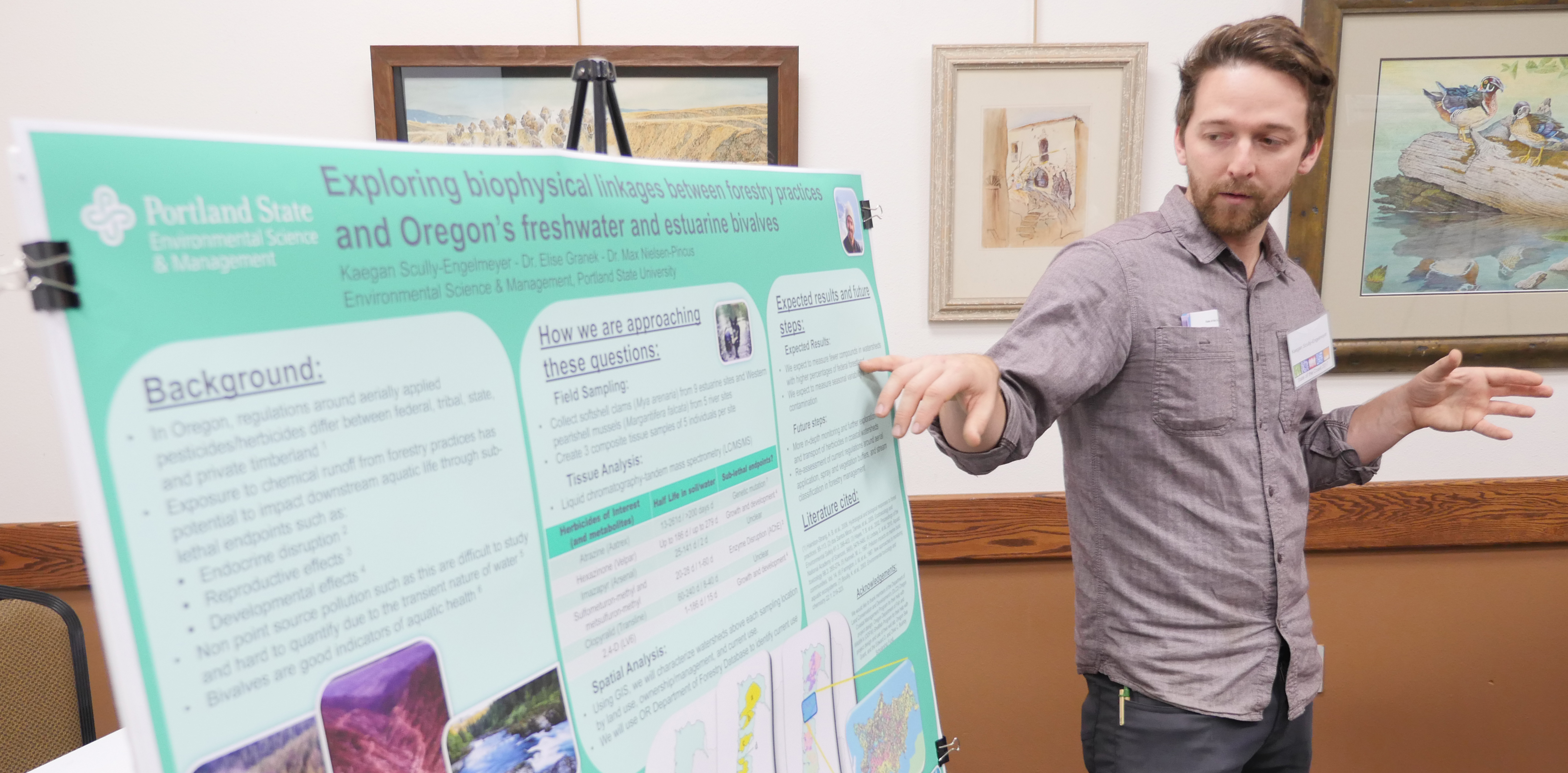 Kaegan Scully-Engelmeyer explains his research while standing in front of a poster