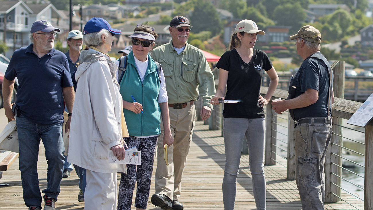 A woman with a black t-shirt with an Oregon Sea Grant logo stands on a pier with a group of other people. The group is chatting while they gather to take a Shop at the Dock tour in Newport, Oregon.