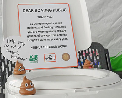 Display with boating toliet and poop emojis figurines explains to recreational boaters the proper disposal of onboard sewage.