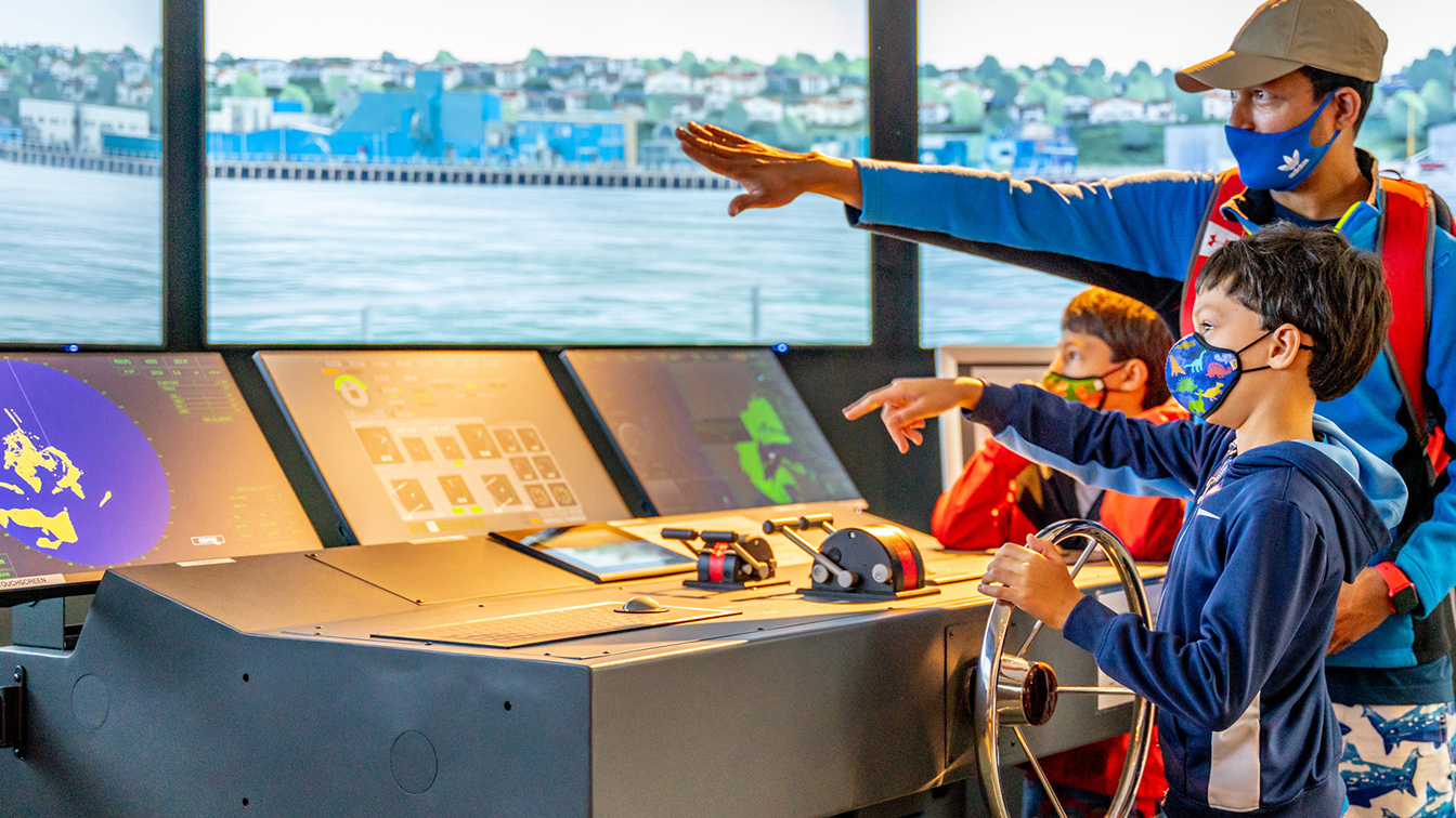 Using a simulator, a child steers a research ship through Yaquina Bay in an exhibit at the Hatfield Visitor Center. His father stands near him and points to the screen in front of them.
