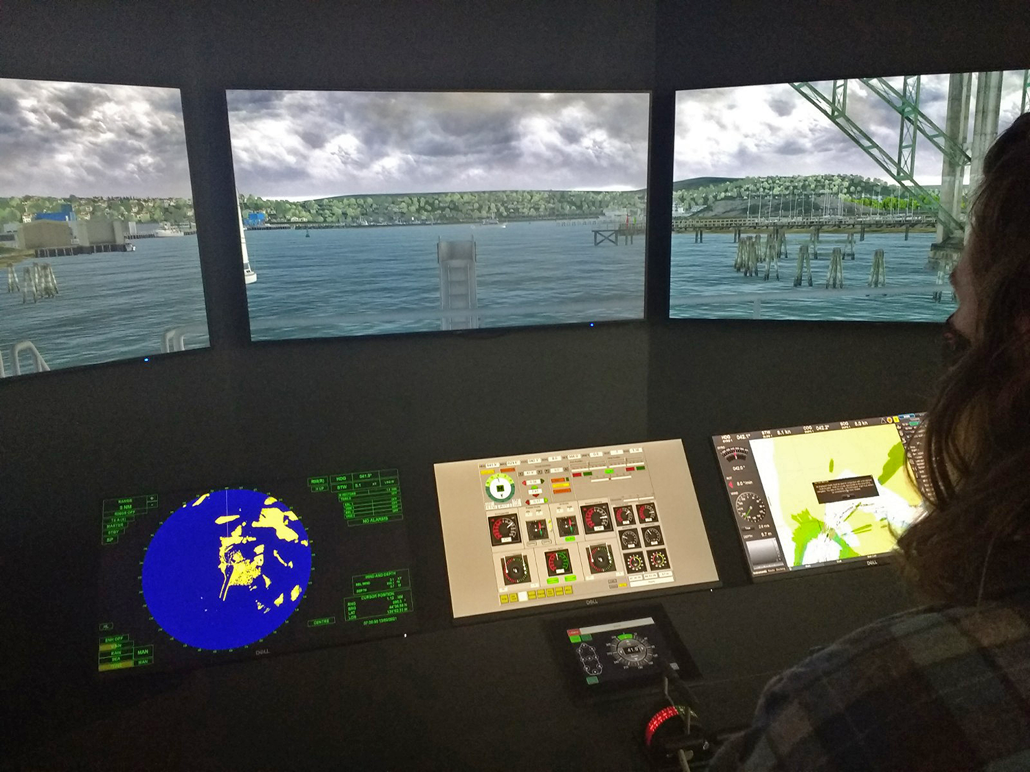 A young woman stands at the wheel of a simulation for driving large research vessels in and out of the harbor.
