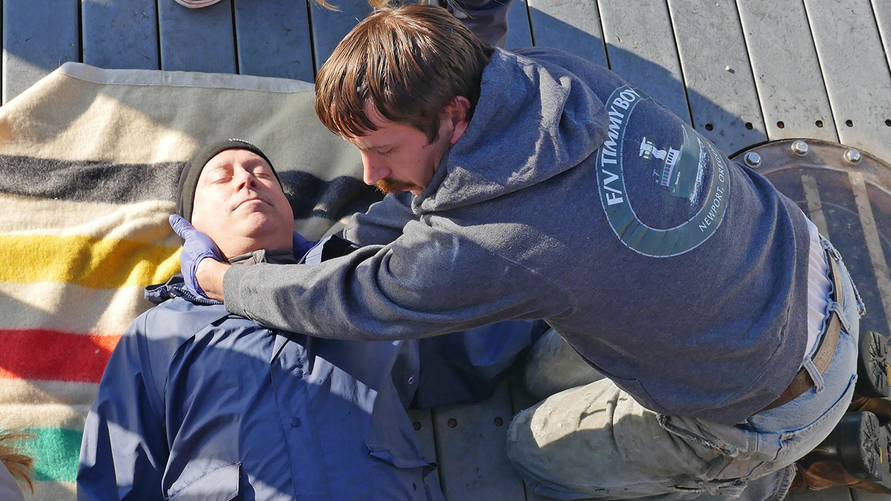 Two men practice a saftey training simulation on a boat deck. One man lies on a blanket with his eyes closed. The other, wearing latex gloves, places his hands under the prone man's head.