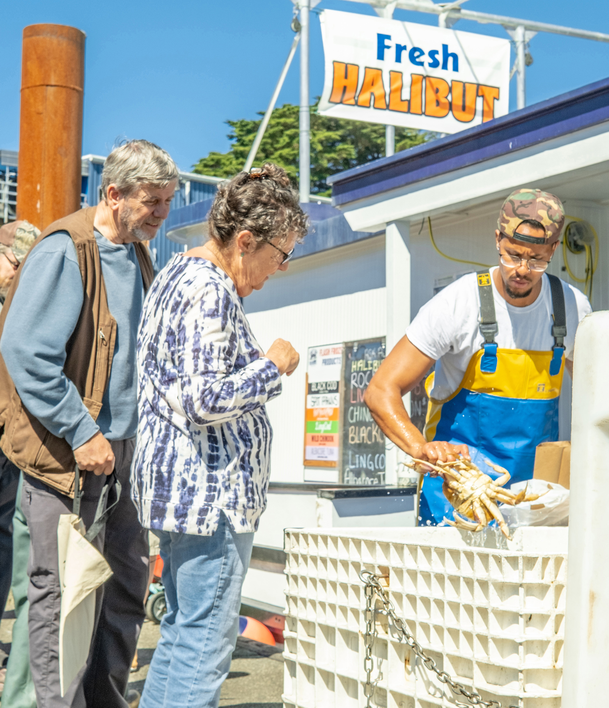 A worker on a dock shows a Dungeness crab to two people.