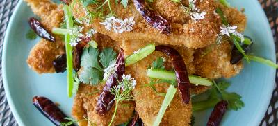 Breaded and fried fish on a blue plate with peppers, celery, and cilantro garnish