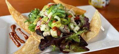 plate with black cod ceviche on a bed of lettuce and chips