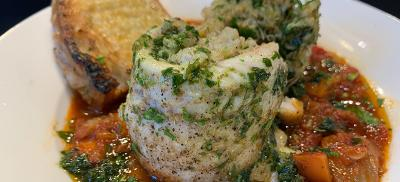 Shallow bowl with a sole fish filet stuffed with crab sitting on cooked vegetable sauce.