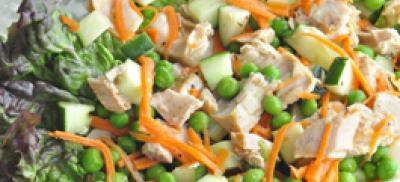 A plate of tuna salad with peas and carrots, served over lettuce