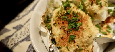 Breaded fish in foil with parsley garnish