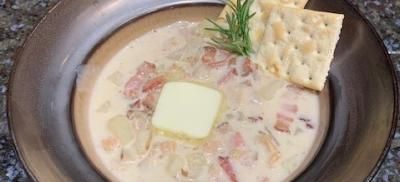 A bowl of creamy clam chowder with butter, saltines, and rosemary.