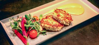 plate of crab cakes with vegetables and dipping sauce.