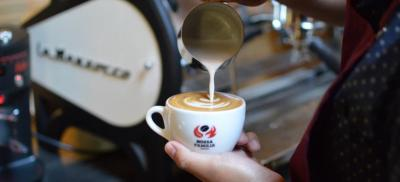 close up of a barista making a latte in a cup with Nossa Familia Coffee logo