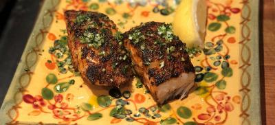 Two filets of blackened black cod on a colorful hand-painted plate.