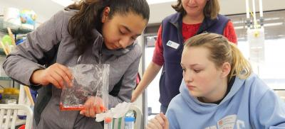 two high school girls work on a marine science experiment, teacher looks on