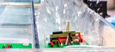 Water crashed against a Lego structure in the tsunami wave tank