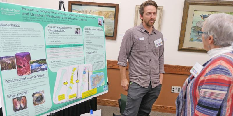 Student Kaegan Scully-Engelmeyer explains his research while standing in front of a poster