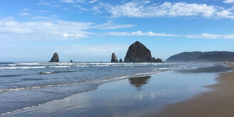 View of Haystack Rock, a seastack in the Pacific Northwest coast, on a clear day at the beach.
