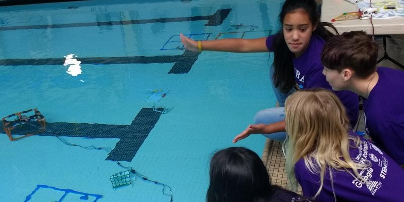 Student work together poolside to operate underwater rover at MATE ROV competition.