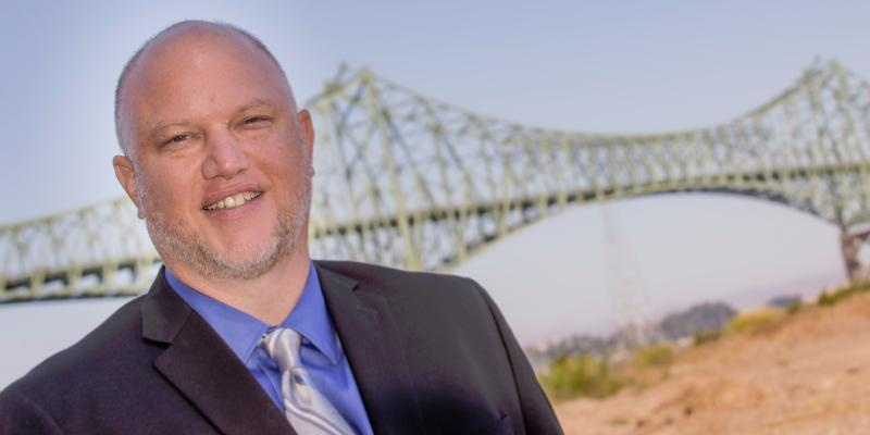 Miles Phillips stands near the bridge that spans Coos Bay.