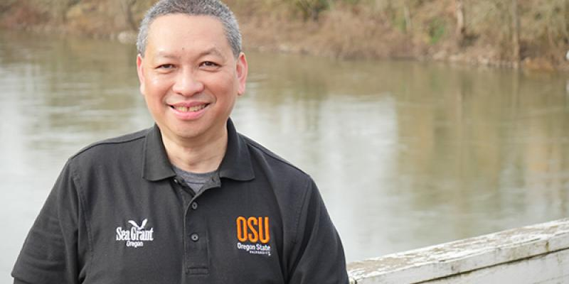 Sam Chan, Oregon Sea Grant Extension, stands by marsh