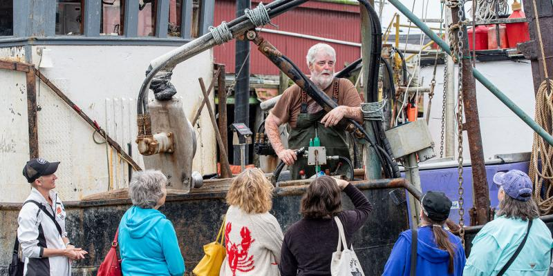 Fisherman Kenny Bushnell stands on his boat and talks to participants in a Shop at the Dock tour in Garibaldi, Oregon