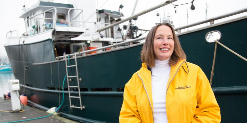 Michele Longo Eder stands in front of a fishing boat