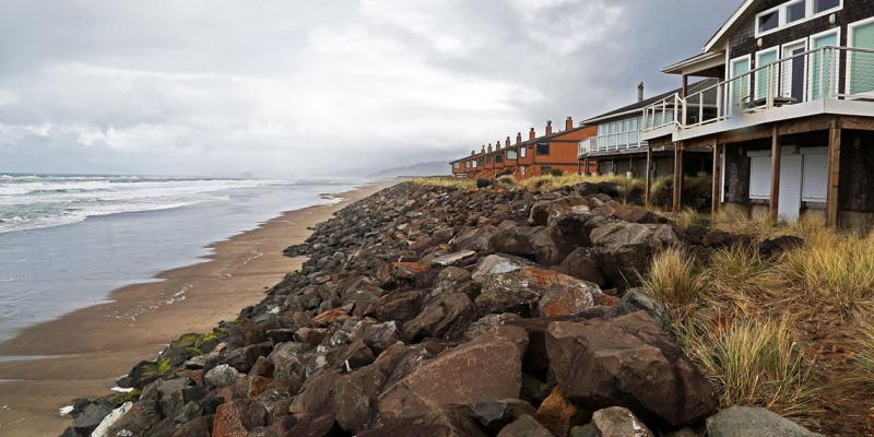Oceanfront homes with boulders piled along the front to protect them from erosion.