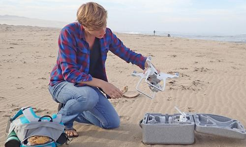 Alexandra Simpson kneels on the beach while holding a drone.