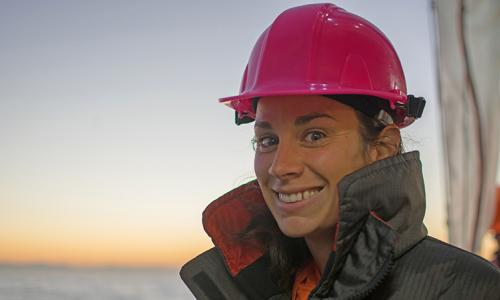 Anna Bolm stands on a boat wearing a pink hard hat.