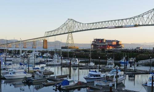 Boat in Astoria harbor with a large bridge in the background at sunset