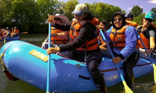 Students rafting down the Willamette River on a sunny day