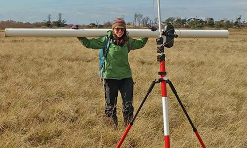 Researcher Erin Peck stands in a marshy field holding a long coring tube.