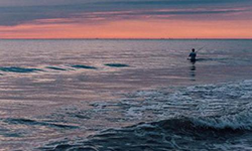 Man fishes on ocean shore at sunset