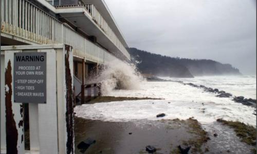 picture of flood warning sign at the beach with waves crashing into a building