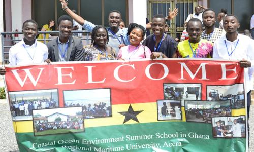 """Adult students stand behind a banner that says, """"Welcome Coastal Ocean Environmental School in Ghana"""""""
