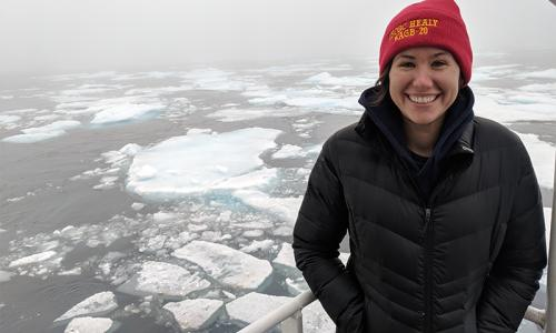 Kristin Beem, stands on the deck on an ocean research vessel. There is ice in the water and she is dressed in winter clothes.
