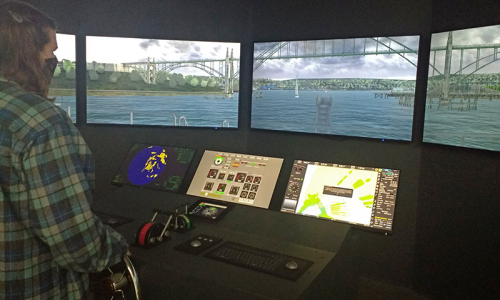 A woman stands at the helm of a boat simlators. Screens in front of her show a 180-degree view of Yaquina Bay.