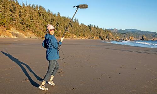 Film maker Saskia Madlener carries a boom mic across the beach