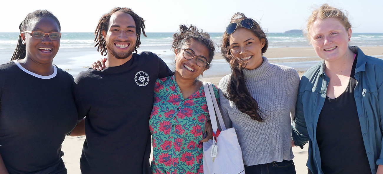 Five college-aged students stand with their arms around each other and smile. They are standing on Beverly Beach in Oregon. The ocean is in the background and it is a sunny day.