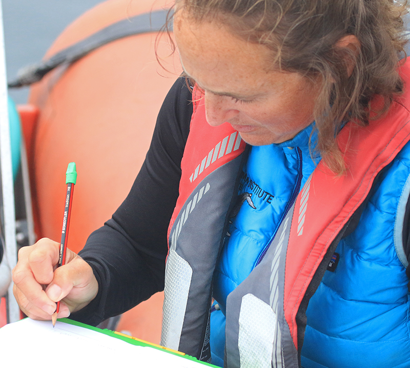 Whale researcher Leigh Torres takes notes in a log book.
