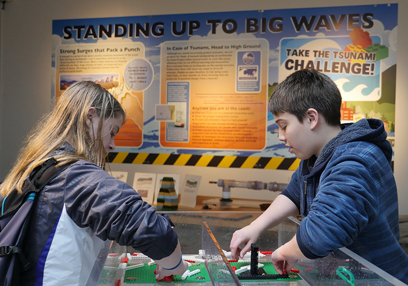 High school students build Lego structures in the tsunami wave tank at the Visitor Center.